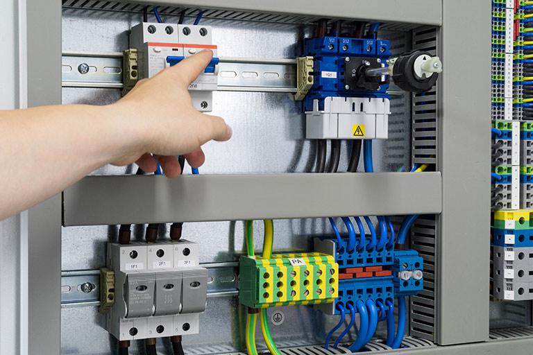 Eine Hand an einem Schalter eines Überspannungsschutz
